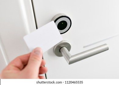 Hotel door - Young man holding a keycard in front of the electronic sensor of a room door. Concept travel or business trip