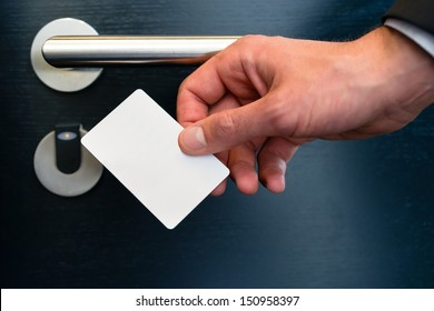 Hotel door - Young man holding a keycard in front of the electronic sensor of a room door