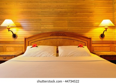 Hotel double bed with flowers on pillow, lighting lamps. Front view.