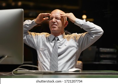 Hotel elderly male manager made a mistake in the bill. Man in stress in front of a computer.