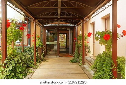 Hotel entrance with potted plants and red flowers under and Walkway Canopy – Walkway Cover