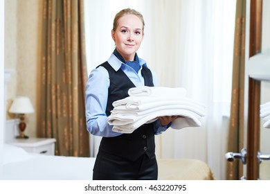 Hotel female housekeeping worker with linen