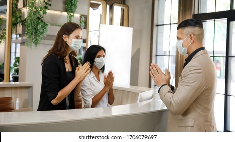 hotel guest and receptionist wearing mask to protect from conronavirus covid 19 having new practice of greeting with thai wai, new greeting practice in coronavirus covid 19 pandemic