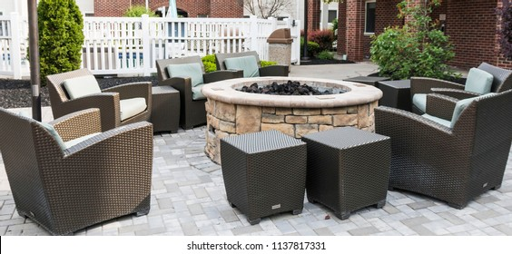A hotel has a comfortable outside area to relax with friends and family with a fire pit and plenty of chairs.