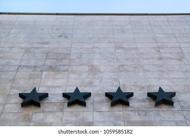 Hotel and hospitality / Four stars on the stone wall of the hotel / Quality of hotel and motel services / In the background of the blue sky.