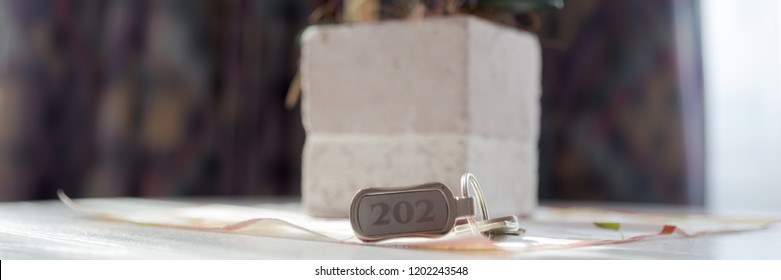 Hotel key number 202 on the table in the room