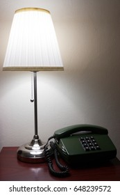 Hotel lamp and a telephone on reddish furniture.