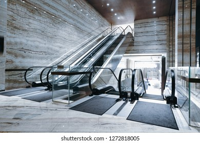 Hotel lobby with escalator and marble floors and walls