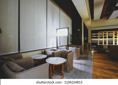 Hotel lobby interior with reception desk, marble floor and crystal lamp, sofas and long bar.