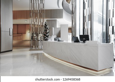 Hotel lobby interior with reception desk, sofas, marble floor and long bar.