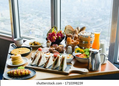 Hotel luxury room romantic breakfast with plenty of food and drinks at table near window - croissants, fruits, sandwiches, grilled meat, tea, juice, coffee, eggs
