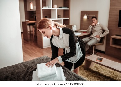 Hotel maid. Beautiful hotel maid wearing white and black uniform bringing white towels in the morning