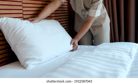 Hotel maid making the bed in the luxury hotel room ready for tourist travel.