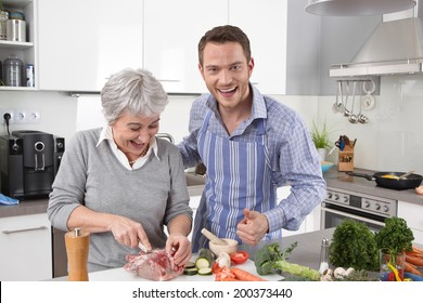 Hotel mama: young man and older woman cooking together roast pork.