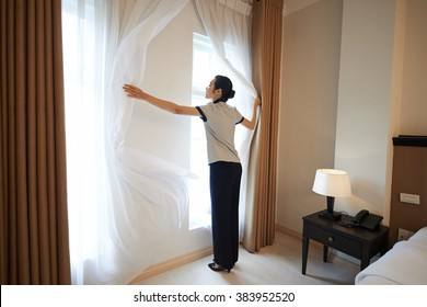 Hotel manager adjusting curtains in the room