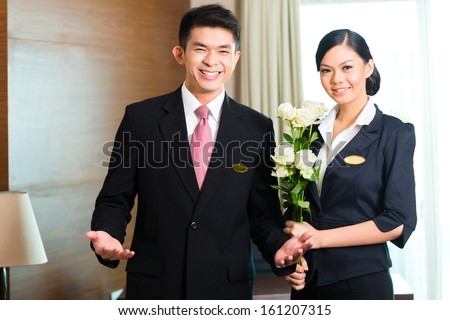 Hotel Manager or director and supervisor welcome arriving VIP guests with roses on arrival in luxury or grand hotel