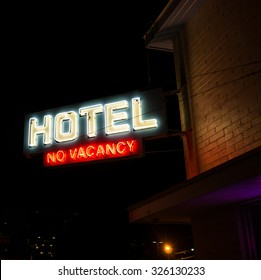 "Hotel No Vacancy Neon Sign. Vintage neon ""hotel no vacancy"" sign in front of an old hotel."