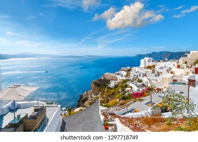 A hotel patio offers a view of the Aegean Sea, rocky cliffs, whitewashed buildings and Santorini caldera from a hillside overlook in Oia, Greece.