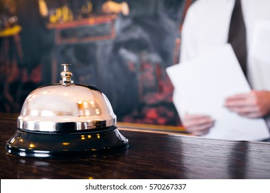 Hotel reception service bell with concierge holding a file in background