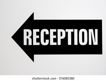 Hotel reception signage in balck and white. Reception is in an arrow