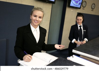 Hotel receptionist. Modern luxury hotel reception counter desk with bell. Two happy females receptionist worker standing at hotel counter.