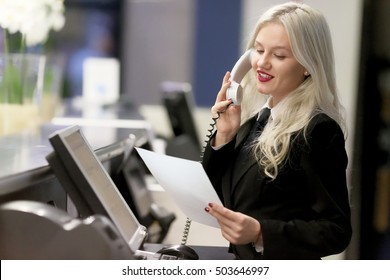 Hotel receptionist. Modern luxury hotel reception counter desk with bell. Happy females receptionist worker standing at hotel counter.