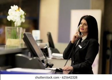 Hotel receptionist. Modern luxury hotel reception counter desk with bell. Happy female receptionist worker standing at hotel counter.