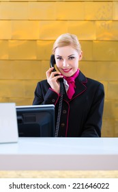 Hotel receptionist with phone on front desk