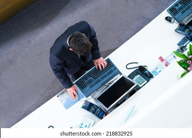Hotel receptionist working on computer at front desk office