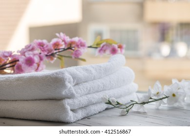 Hotel, resort, spa or luxury concept - Beauty and wellness - Towels and orchid against a sunny background.