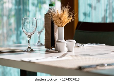 Hotel restaurant table setting with cute decoration, wine glass, salter, bottle of water in low angle perspective with sun light through wibdow