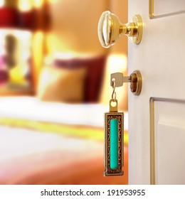 Hotel room or apartment doorway with key and keyring key fob in open door and bedroom in background