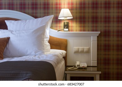 Hotel room - bed with pillow and lamps.