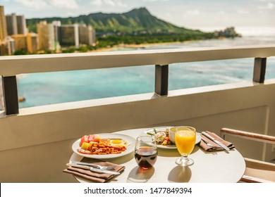 Hotel room breakfast on balcony view of Waikiki beach, Honolulu, Hawaii. Vacation travel morning food American breakfast in luxury resort outside.