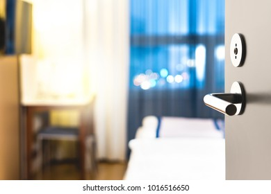 Hotel room door open. Clean and elegant accommodation service. Close up of handle. Bed, table and tv. Travel, lodging and motel concept.