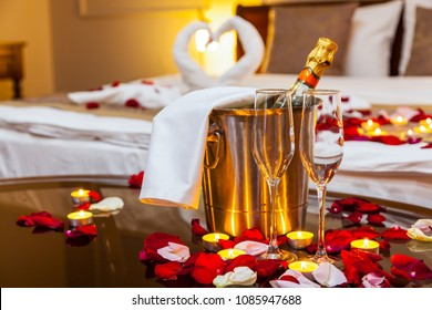 Hotel room for a honeymoon: a table with a fruit plate and candles, in the background a bed decorated with swans of towels and rose petals