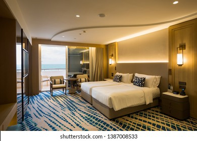 Hotel room interior. Modern hotel. Seaside resort. Sea view. Bedroom interior. Cozy bedroom. Big double bed. Bedroom furniture.