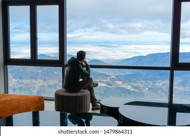 Hotel room with mountain landscape view from window, interiors with chairs and table, and a man sits seeing the scene through window