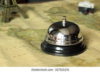 Hotel service bell on a world map in a vintage decorate with a camera and a monument on the background. Travel and accommodation concept.