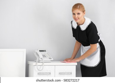 Hotel service concept. Chambermaid cleaning bedside chest with wiper