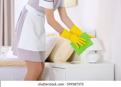 Hotel service concept. Chambermaid cleaning lamp on bedside table from dust