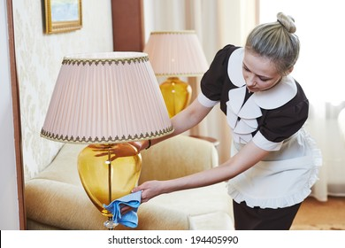 Hotel service. female housekeeping worker with cleaning table from dust in room