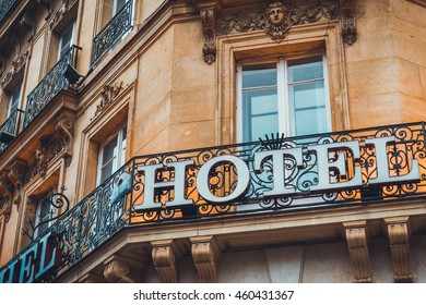 Hotel sign on ornate wrought iron work around a corner angle balcony on an old historic stone building