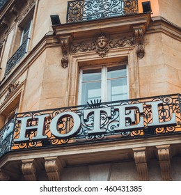 Hotel sign on an ornate wrought iron balustrade on a corner window in an old historic stone building, low angle view