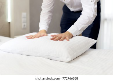 hotel staff setting up pillow on bed