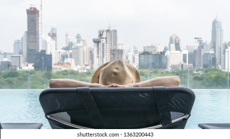 Hotel stay relaxation of business woman take it easy happily resting on beach chair on holiday travel vacation at swimming pool poolside in peacefully with city park rooftop view and summer sunny sky