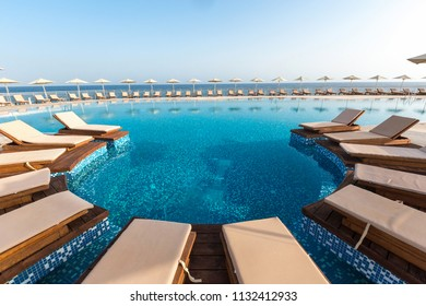 Hotel swimming pool, outdoor, with sunbeds around