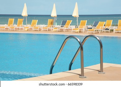 hotel swimming pool with stair, yellow lounges and umbrellas