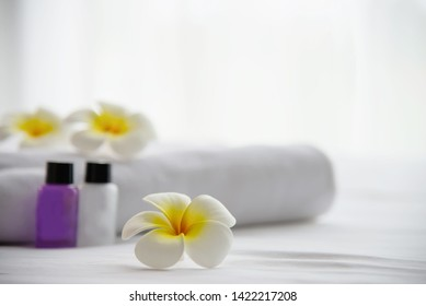 Hotel towel and shampoo and soap bath bottle set on white bed with plumeria flower decorated - relax vacation at the hotel resort concept