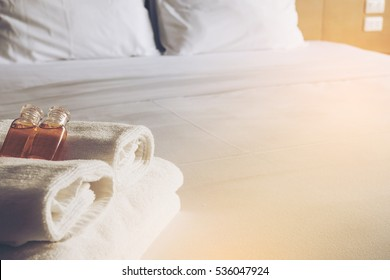 Hotel towel with shampoo and soap bottle set on white bed